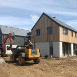 J and S Building Contractor staff on a digger next to new build property