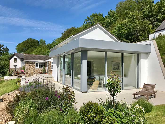 modern home with extension and bifold doors opening to landscaped garden